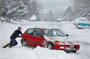 Alex Vlasity helps push out a passing car which became bogged on an unplowed road after a night of heavy snowfall, in Boulder, Colo., Tuesday, Dec. 15, 2015. The biggest winter storm to hit the Denver area so far this season has left most schools closed and created some havoc on the roads for those forced to commute.