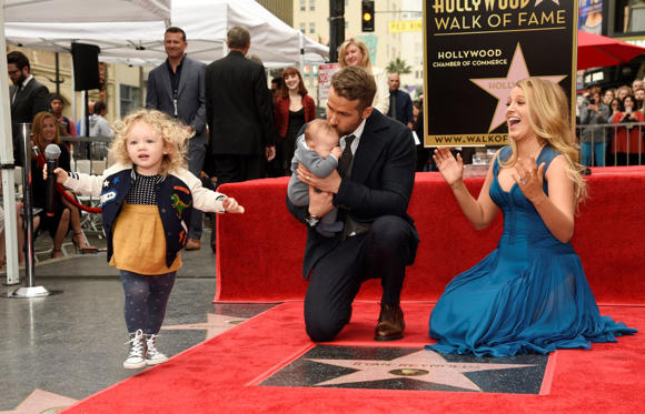 שקופית 2 מתוך 29: James Reynolds, left, daughter of Ryan Reynolds, steals the microphone as Reynolds poses wih his wife Blake Lively and their youngest daughter during a ceremony to award him a star on the Hollywood Walk of Fame on Thursday, Dec. 15, 2016, in Los Angeles.