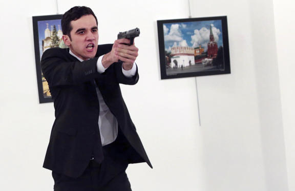 An unnamed gunman gestures after shooting the Russian Ambassador to Turkey, Andrei Karlov, at a photo gallery in Ankara, Turkey, Monday, Dec. 19, 2016. The Russian foreign ministry spokeswoman said he was hospitalized with a gunshot wound.
