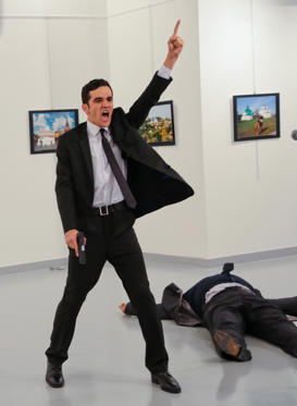 An unnamed gunman gestures after shooting the Russian Ambassador to Turkey, Andrei Karlov, at a photo gallery in Ankara, Turkey, Monday, Dec. 19, 2016. A gunman opened fire on Russia's ambassador to Turkey at a photo exhibition on Monday. The Russian foreign ministry spokeswoman said he was hospitalized with a gunshot wound.