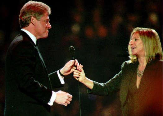 Diapositiva 12 de 17: LANDOVER, UNITED STATES:  Entertainer Barbra Streisand (R) hands the microphone to U.S. President-elect Bill Clinton as he takes the stage to address the crowd gathered for a televised inaugural gala at the Capital Centre in suburban Maryland late 19 January 1993. (Photo credit should read POOL/AFP/Getty Images)