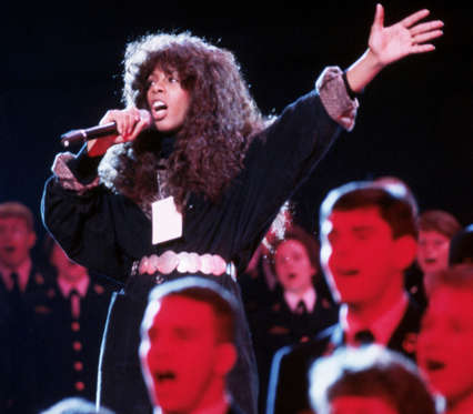 Diapositiva 15 de 17: Donna Summer sings a song with a military choir at the inaugural celebration for President Ronald Reagan in 1985. The festivites were moved indoors due to severely cold weather. (Photo by © Wally McNamee/CORBIS/Corbis via Getty Images)