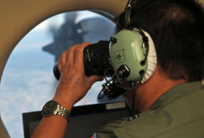 FILE - In this March 22, 2014, file photo, Flight Officer Jack Chen uses binoculars at an observers window on a Royal Australian Air Force P-3 Orion during the search for missing Malaysia Airlines Flight MH370 in Southern Indian Ocean, Australia.