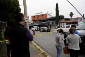 People stand outside the Colegio Americano del Noreste after a student opened fire at the American school in Monterrey, Mexico, on Wednesday.