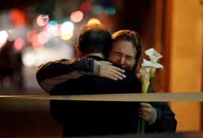 Mourners embrace near the site of a warehouse fire Sunday, Dec. 4, 2016, in Oakl...