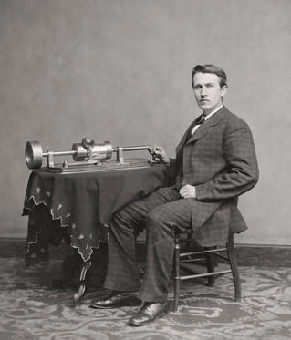 Slide 1 of 8: American inventor and businessman, here seen seated by his 1877 invention, the phonograph.