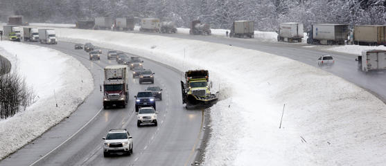 A snowplow makes its way along an eastbound lane of Interstate 90 as trucks on the westbound lane behind are parked while drivers remove chains on Dec. 22, 2015, at Snoqualmie Pass, Wash.