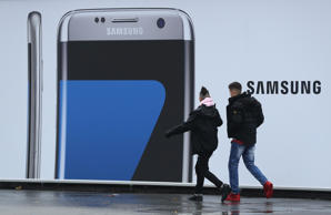 People walk past an advertisement for the Samsung Galaxy S7 Edge smartphone on N...