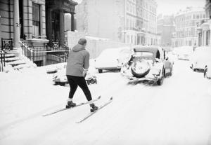 29th December 1962:  A skier being pulled along behind a car in Earl's Court, London.  (Photo by Terry Fincher & Michael Stroud/Express/Getty Images)