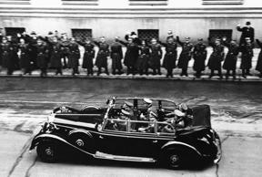Adolf Herr Hitler, riding beside the driver, goes to the Reichstag in Berlin to tell the German people that papers have been handed the American representative on Dec. 11, 1941. Hitler passes in front of the Foreign Office inside which U.S. Charge D'Affa