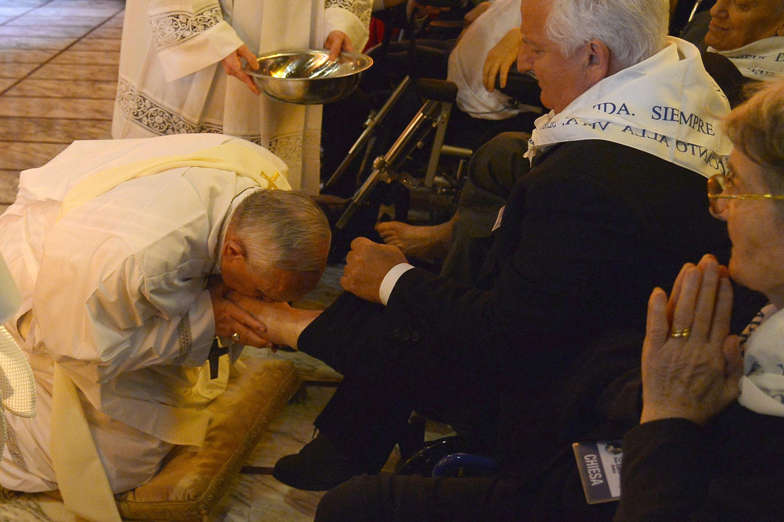 Diapositiva 4 de 23: Pope Francis (L) kisses the foot of a man as he performs the traditional Washing of the feet during a visit at a center for disabled people as part of  Holy Thursday (Maundy Thursday) as part of the Holy Week on April 17, 2014 in Rome.  AFP PHOTO / ALBER