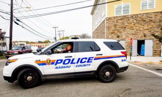 A Nassau County Police officer sits in front of a crime scene at 130 Secatogue A...