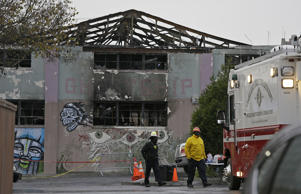 "FILE - This Wednesday, Dec. 7, 2016 file photo shows Oakland fire officials walk past the remains of the Ghost Ship warehouse damaged from a deadly fire in Oakland, Calif. The Dec. 2 fire killed dozens of people during a electronic dance party, after it raced through the building, trapping them inside. For those who survived, it was largely a matter of luck that when the first cries of ""fire"" were heard, they were able to find their way through smoke and darkness or were near enough to a door or already outside."