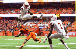 Louisville Cardinals quarterback Lamar Jackson (8) leaps over Syracuse Orange defensive back Cordell Hudson (20) during the second quarter at the Carrier Dome.