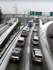 Traffic on Interstate 84 comes to a standstill on a sloped, icy ramp merging with Interstate 5 in Portland, Ore., Thursday, Dec. 8, 2016, as the first winter storm of the season hits the region.