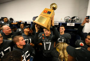 The Knights Stephen Johnson (17) celebrates with the Secretary's Trophy after defeating the Navy 21-14.