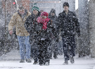 Commuters arriving at the La Salle Street METRA rail station walk into a lake effect snow storm Thursday, Feb. 26, 2015, in Chicago.