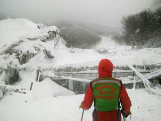 A member of Lazio's Alpine and Speleological Rescue Team stands in front of the Hotel Rigopiano in Farindola, central Italy, hit by an avalanche, in this January 19, 2017 handout picture provided by Lazio's Alpine and Speleological Rescue Team.