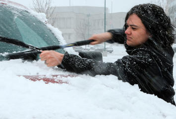 File: A woman clears snow off of her car