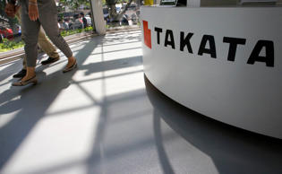 FILE - In this May 4, 2016, file photo, visitors walk by a Takata Corp. desk at an automaker's showroom in Tokyo. New Mexico Attorney General Hector Balderas has announced a lawsuit against Japanese manufacturer Takata and a long list of auto makers in connection with the sale of cars with dangerous air bag inflators. The attorney general's office argues in a lawsuit being filed Friday, Jan. 20, 2017 that the manufacturers had a duty to ensure their products were safe and that concealment of air bag defects amounted to unfair, deceptive and unconscionable trade practices under New Mexico law. (AP Photo/Shizuo Kambayashi, File)