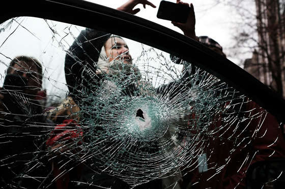 Slide 4 of 110: People stand around a window of a car damaged by protesters as police and demonstrators clash in downtown Washington following the inauguration of President Donald Trump on January 20, 2017 in Washington, DC. Washington and the entire world have watched the transfer of the United States presidency from Barack Obama to Donald Trump, the 45th president.
