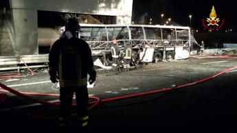 Firefighters inspect the burned hulk of a bus that crashed and burst into flames near Verona, northern Italy, Saturday, Jan. 21, 2017.