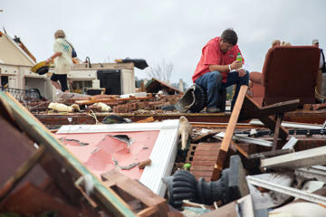 Jeff Bullard sits in what used to be the foyer of his home as his daughter, Jenny Bullard, left, looks through debris at their home that was damaged by a tornado, Sunday, Jan. 22, 2017, in Adel, Ga.