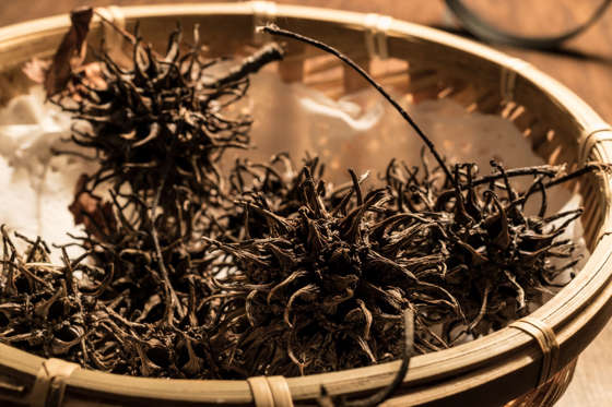 الشريحة 12 من 13: Chinesse Tea Da Hong Pao or Conifer Cone in a wooden bowl.