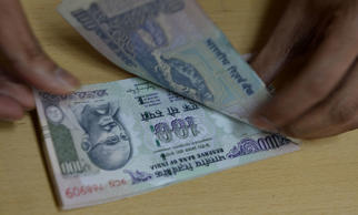 A bank staff member counts Indian 100 rupee notes