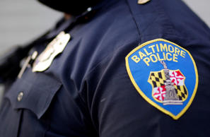Baltimore Police Department Officer stands on a street corner during a foot patrol in Baltimore.