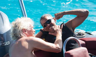 Obama and British businessman Richard Branson sit on a boat during Obama's holid...