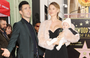HOLLYWOOD, CA - FEBRUARY 10: Recording artist Adam Levine (L), wife model Behati Prinsloo and their daughter attend his being honored with a Star on the Hollywood Walk of Fame on February 10, 2017 in Hollywood, California. (Photo by David Livingston/Getty Images)