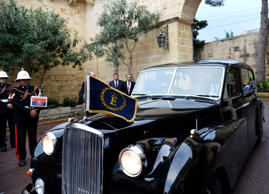 Queen Elizabeth II flanked by Prince Philip arrive aboard an Austin Princess car at San Anton Palace, on November 26, 2015 in Malta. Queen Elizabeth II arrives in Malta for a state visit to the Mediterranean island where she reputedly spent her happiest years as a carefree princess in the early 1950s. British and Maltese flags lined the main street of the capital Valletta ahead of her three-day visit, which will see the queen and her husband Prince Philip attend the opening ceremony of the 24th Commonwealth summit and revisit spots from when they were newlyweds.