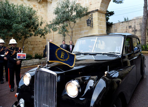22 枚のスライドの 1 枚目: Queen Elizabeth II flanked by Prince Philip arrive aboard an Austin Princess car at San Anton Palace, on November 26, 2015 in Malta. Queen Elizabeth II arrives in Malta for a state visit to the Mediterranean island where she reputedly spent her happiest years as a carefree princess in the early 1950s. British and Maltese flags lined the main street of the capital Valletta ahead of her three-day visit, which will see the queen and her husband Prince Philip attend the opening ceremony of the 24th Commonwealth summit and revisit spots from when they were newlyweds.