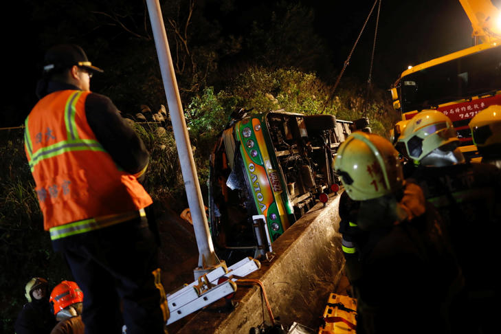 Rescuers gather around a crashed bus in Taipei, Taiwan February 13, 2017.