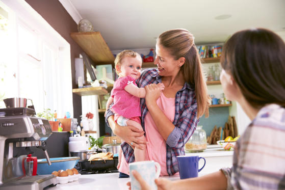 Slide 1 of 10: Mother With Baby Talking To Friend In Kitchen