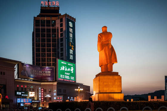 Diapositiva 3 de 40: The Chinese city where you get to do that is called Dandong. I read somewhere it was the most humane of Chinese cities, most having become a polluted nightmare these days... In Dandong, a statue of Mao stands, helplessly witnessing the transition to capitalism all around him, as he keeps pointing with desperation.