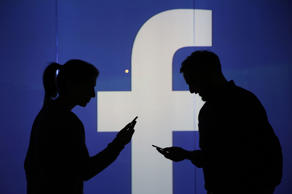 File photo illustrating people checking mobile devices standing near a Facebook Inc. logo.