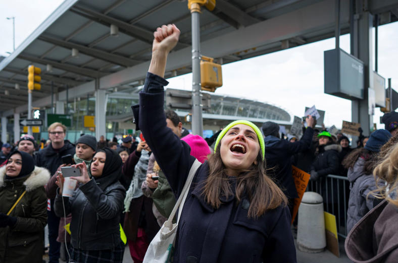 Slide 3 of 14: A protester raises her fist and shouts as she joins others assembled at John F. Kennedy International Airport in New York, Saturday, Jan. 28, 2017 after two Iraqi refugees were detained while trying to enter the country. On Friday, Jan. 27, President Donald Trump signed an executive order suspending all immigration from countries with terrorism concerns for 90 days. Countries included in the ban are Iraq, Syria, Iran, Sudan, Libya, Somalia and Yemen, which are all Muslim-majority nations. (AP Photo/Craig Ruttle)
