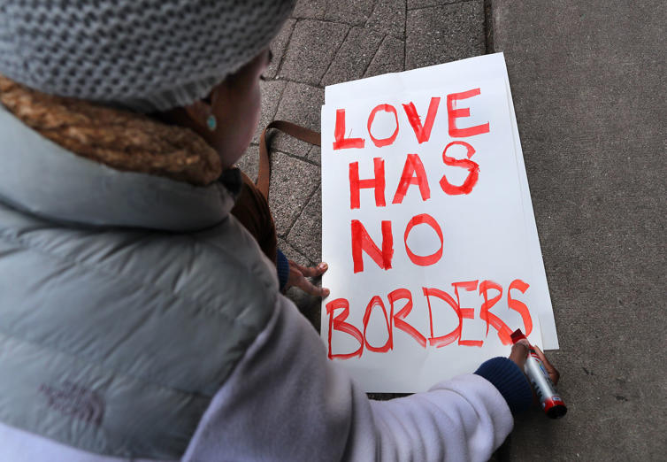 "Slide 12 of 14: BOSTON, MA - JANUARY 28: Tori Furtado, from Boston, kneels down to write a sign that reads, ""Love has no borders,"" in front of the Chinatown Gate, where hundreds gathered for a rally before marching to the State House in a demonstration against President Trump's new immigration order the day after it was issued, Jan. 28, 2017. (Photo by John Tlumacki/The Boston Globe via Getty Images)"