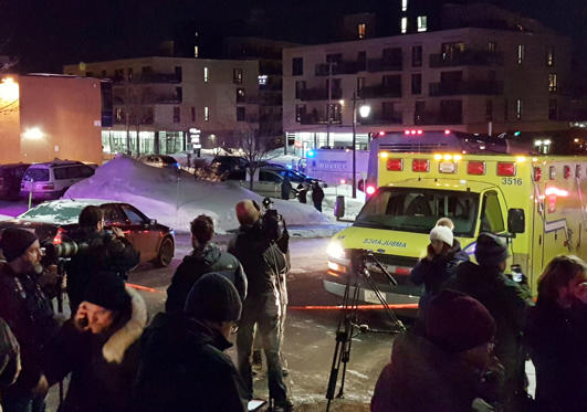 Slide 1 of 7: An ambulance is parked at the scene of a fatal shooting at the Quebec Islamic Cultural Centre in Quebec City, Canada January 29, 2017. REUTERS/Mathieu