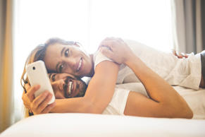 Cuddling couple using cell phone.
