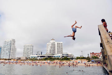In this Jan. 17, 2017 photo, kids play off La Mansa beach in Punta del Este, Uruguay, a coastal city where a Trump Tower is under construction. Opinions about Trump were varied. Among a dozen residents of Uruguay, Argentina, Paraguay and Brazil, there were supporters, critics and those who are simply indifferent. (AP Photo/Matilde Campodonico)