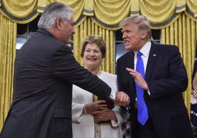TOPSHOT - US President Donald Trump (R) shakes hands with Rex Tillerson (L) as Tillerson's wife Renda St. Clair look on after Tillerson was sworn in as Secretary of State in the Oval Office at the White House in Washington, DC, on February 1, 2017. President Trump notched a victory with confirmation of Rex Tillerson as his secretary of state, but opposition Democrats girded for battle over several other nominations, including his pick for the US Supreme Court.
