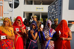 Indian women show their index finger marked with indelible ink after casting their vote at a polling station in Saifai, Etawah, Uttar Pradesh, India.