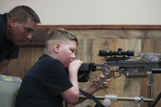 Bill Kohler watches over his son's shoulder as he shoots a target at Xtreme Archery in Springettsbury Township. Ayden was practicing for an upcoming hog and ram hunt. Though cancer has limited his mobility, a special chair with an extended arm helps stabilize the bow so Ayden can still shoot.