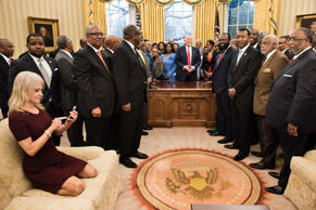 TOPSHOT - Counselor to the President Kellyanne Conway (L) checks her phone after taking a photo as US President Donald Trump and leaders of historically black universities and colleges pose for a group photo in the Oval Office of the White House before a