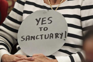 A Florida activist holds a sign in support of immigrants to the U.S. A number of Canadian cities have declared themselves sanctuaries for undocumented migrants.