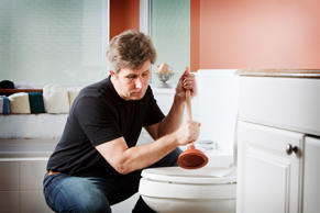 Handyman using plunger to clear a toilet