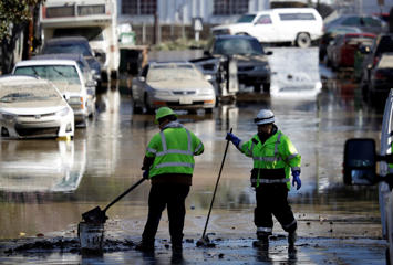 Crews shovel mud in a flooded street Thursday, Feb. 23, 2017, in San Jose, Calif. Thousands of people who had evacuated returned home Thursday amid warnings to be careful about hygiene and handling food that may have come into contact with floodwater.